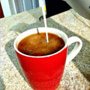 pouring homemade coffee creamer into a red cup filled with coffee