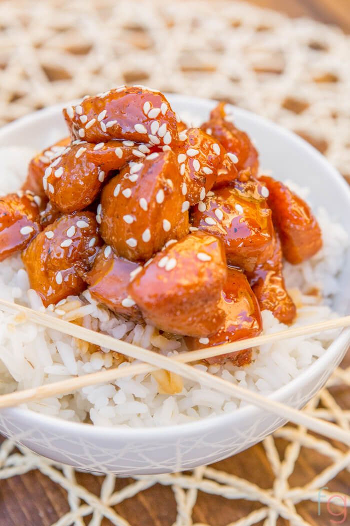 bowl of teriyaki chicken over a bed of white rice, two chopsticks and sprinkled with sesame seeds