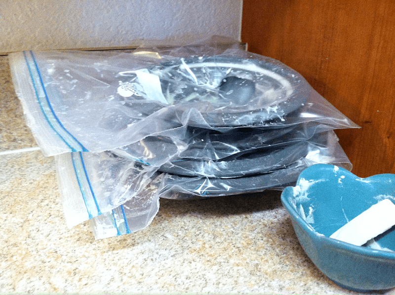 drip pans in ziplock bags soaking in the dish soap and baking soda paste to loosen the remaining gunk