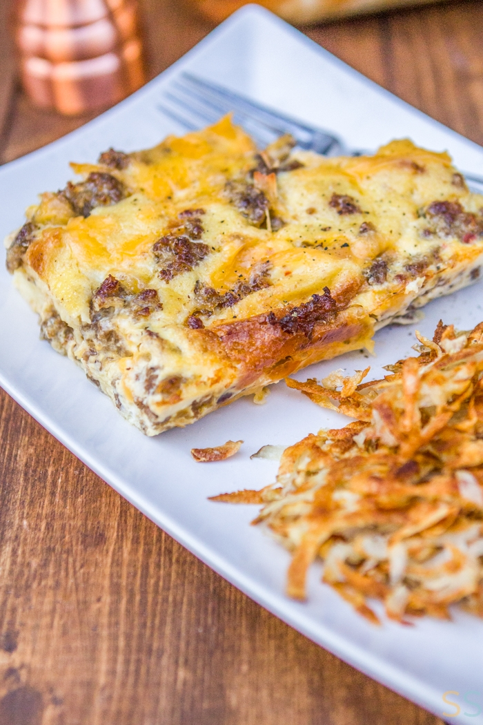 slice of the breakfast casserole with some hash browns on a white plate