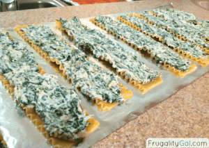 spinach mixture spread on cooked lasagna noodles on a piece of foil ready for the freezer