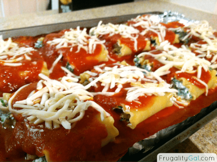Spinach Lasagna Rolls ready to go into the oven.  Topped with sauce and shredded cheese on a sheet pan