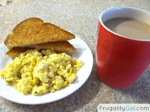 Eggs and toast on a plate with a red cup of coffee and creamer