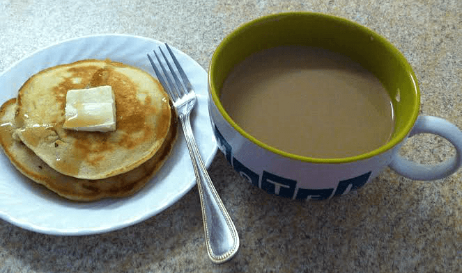 Pancakes with a pad of butter and syrup, a fork and a cup of coffee