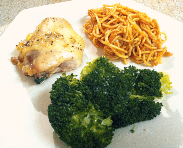 broccoli, spaghetti and a chicken thigh on a plate