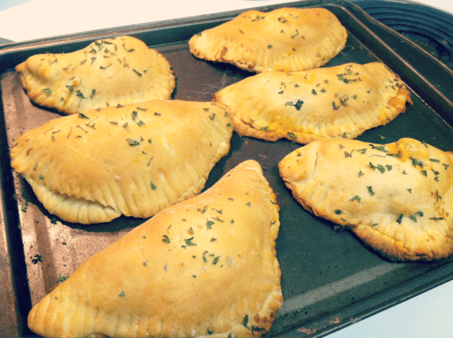 six inexpensive pizza pockets on a baking sheet