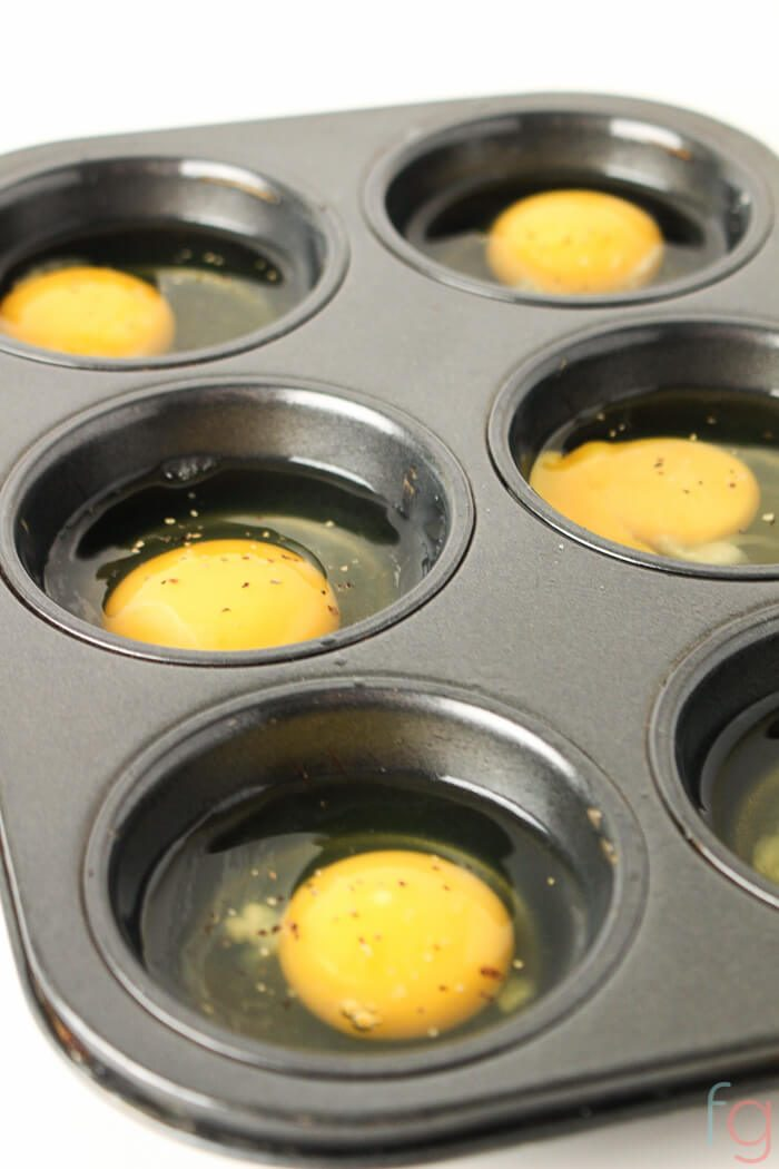 muffin tin with cracked eggs and a bit of pepper