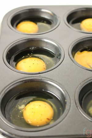 Bake Ahead Eggs with fresh eggs cracked into a muffin tin and ready for baking