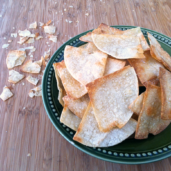 Homemade baked tortilla chips in a green bowl with some crumbles on the wooden counter