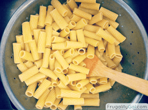 Large bowl with freshly boiled pasta and a wooden spoon. It is mixed with a bit of olive oil to prevent sticking