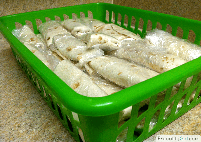 Vegetarian Breakfast Burritos wrapped and in a container for the freezer to make it easy to grab and go in the morning
