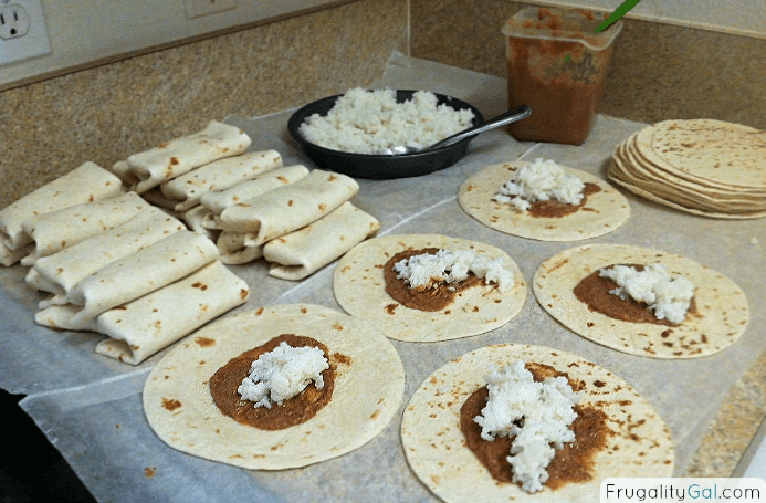 flour tortillas laid out with refried beans and rice in an assembly line