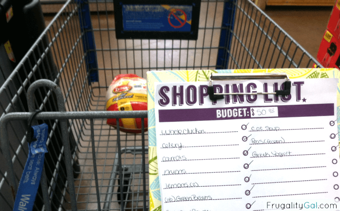 grocery cart with a large whole chicken in it and a shopping list in front