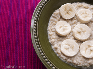 Green bowl with the oatmeal and bananas for breakfast
