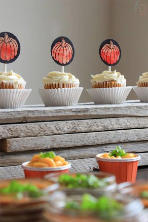 adorable pumpkin cupcake toppers glued to popsicle sticks and stuck in a row of cupcakes