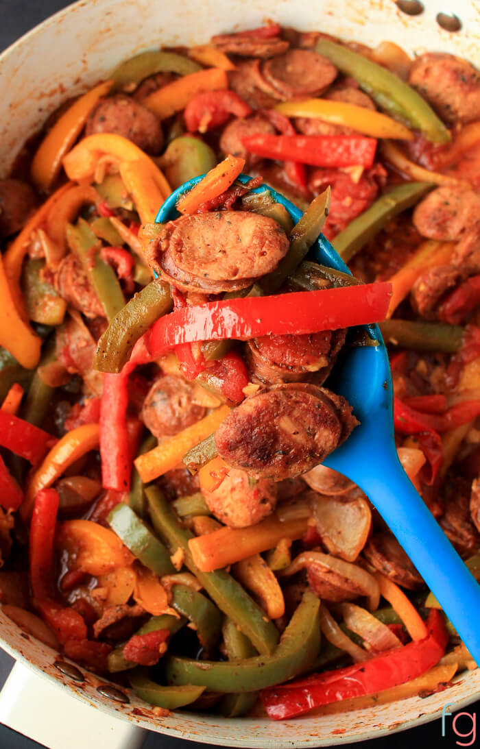 skillet filled with browned sausages and colorful bell peppers.  A blue spoon is lifting some out of the pan.