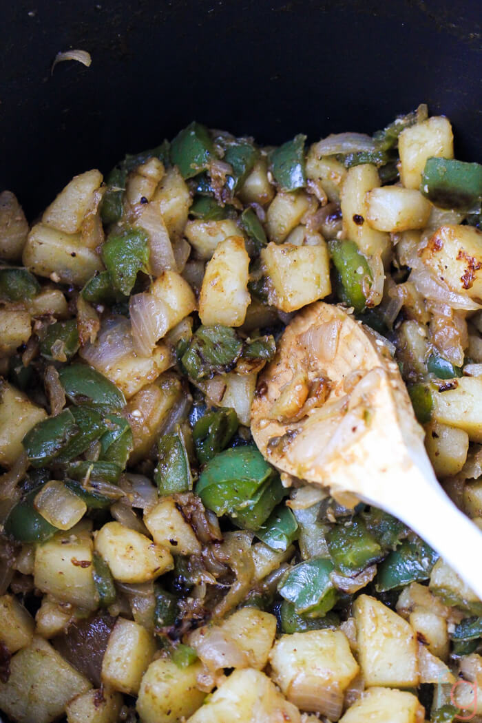 Onions, peppers and potatoes sautéed in a pan.