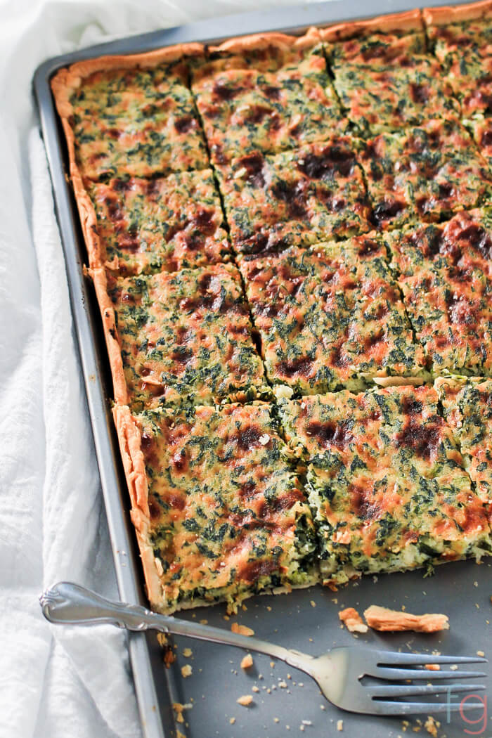 Spinach and Ricotta Slab Pie in a sheet pan with slices out and a decorative fork.