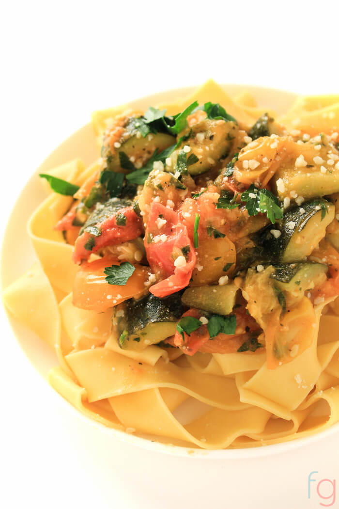 bowl of pasta with fresh tomatoes, zucchini and parley.