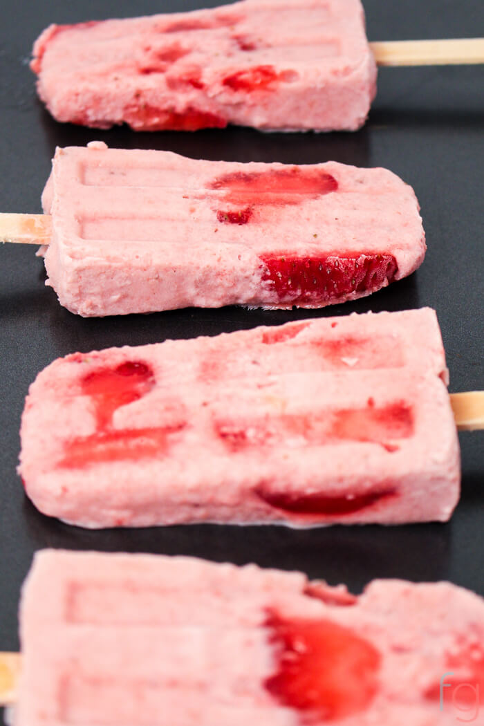 Homemade Strawberry Banana Smoothie Popsicles on a dark counter.