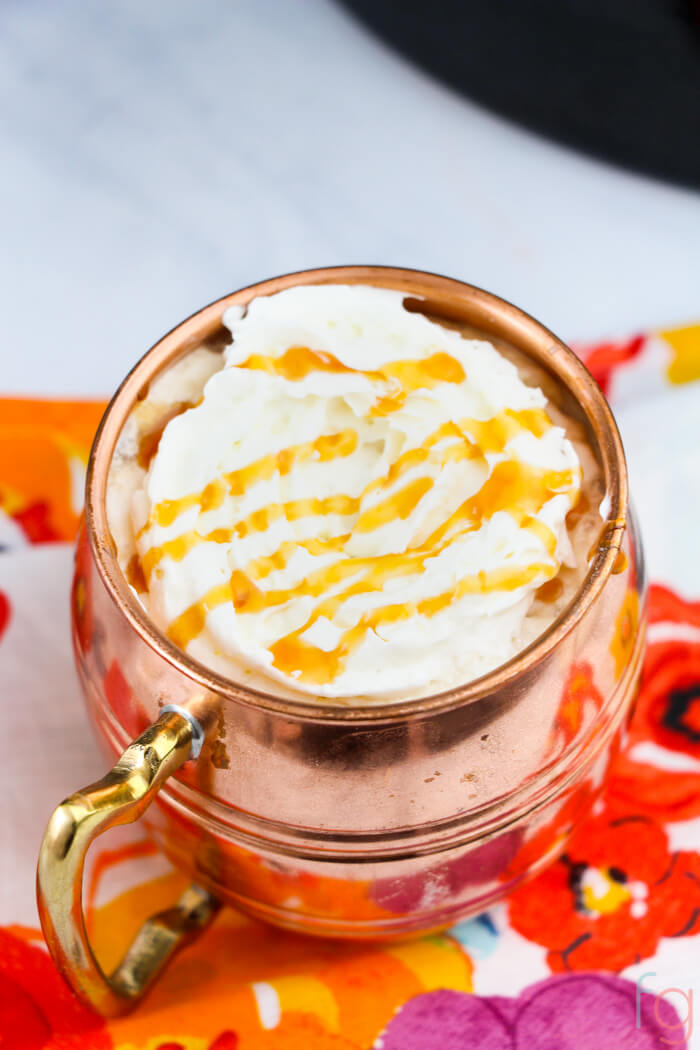 hot latte made in the slow cooker in a copper mug topped with whipped cream and a caramel drizzle.