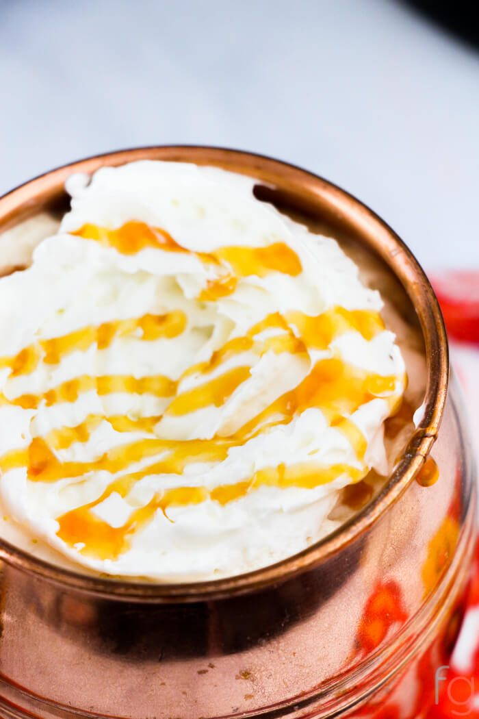 caramel latte in a copper mug with a scrumptious drizzle on the whipped cream.
