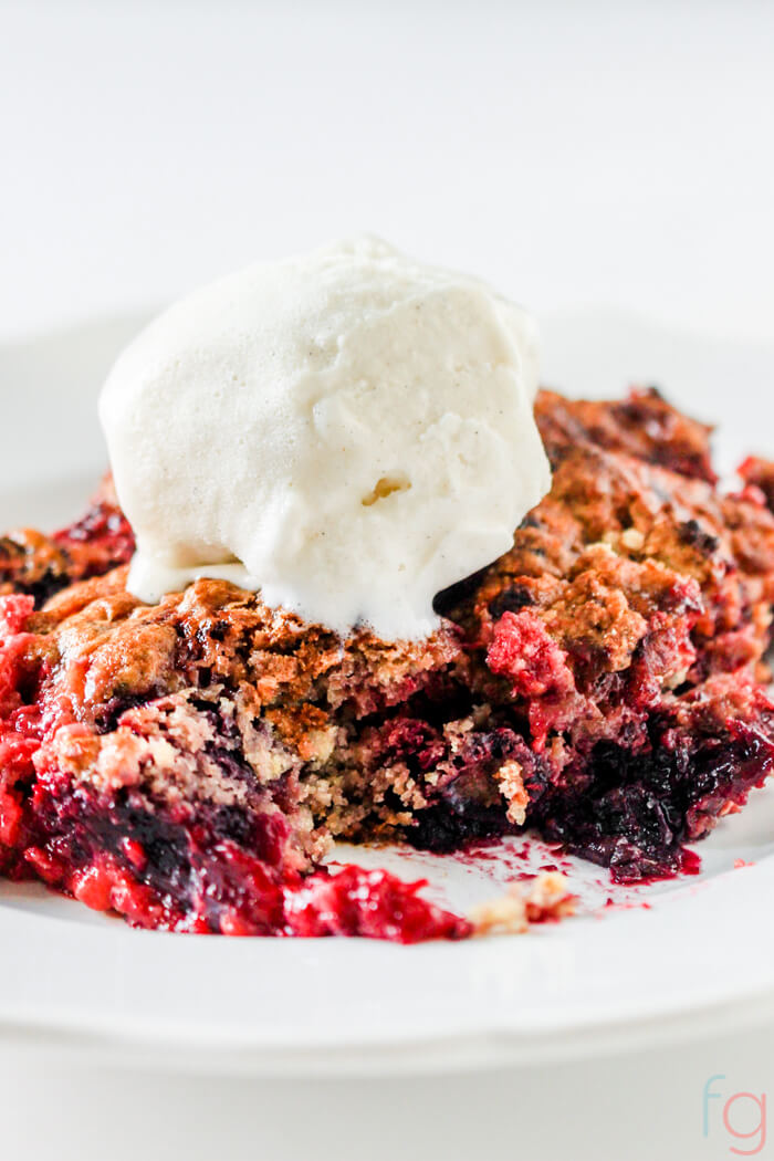 slice of mixed berry dump cake on a white plate with vanilla ice cream.