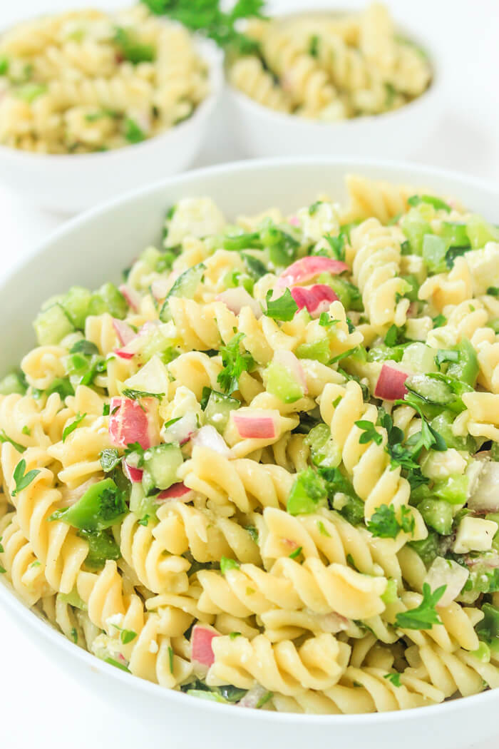 White bowl filled with fresh chopped red onions, pasta and parsley on top.