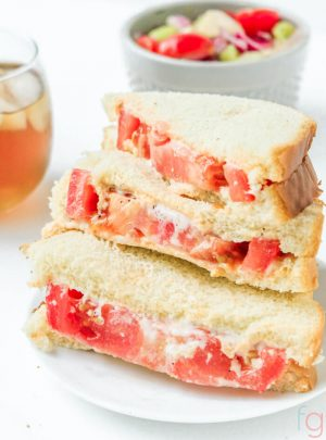 Stack of tomato and mayo sandwiches sliced in half with sweet tea and a salad in the background.