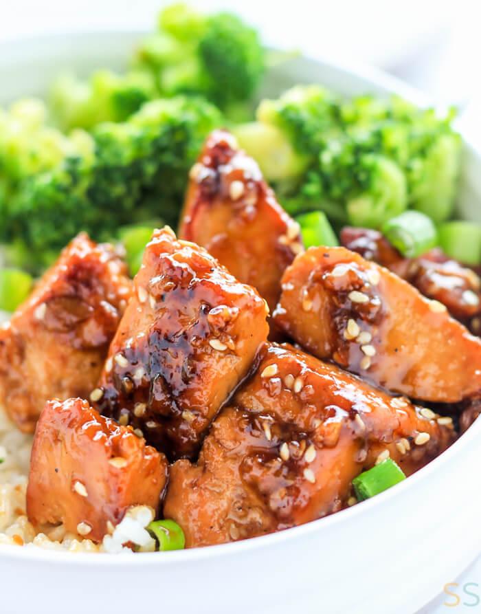 Closeup of the teriyaki covered tofu in a bowl of rice.
