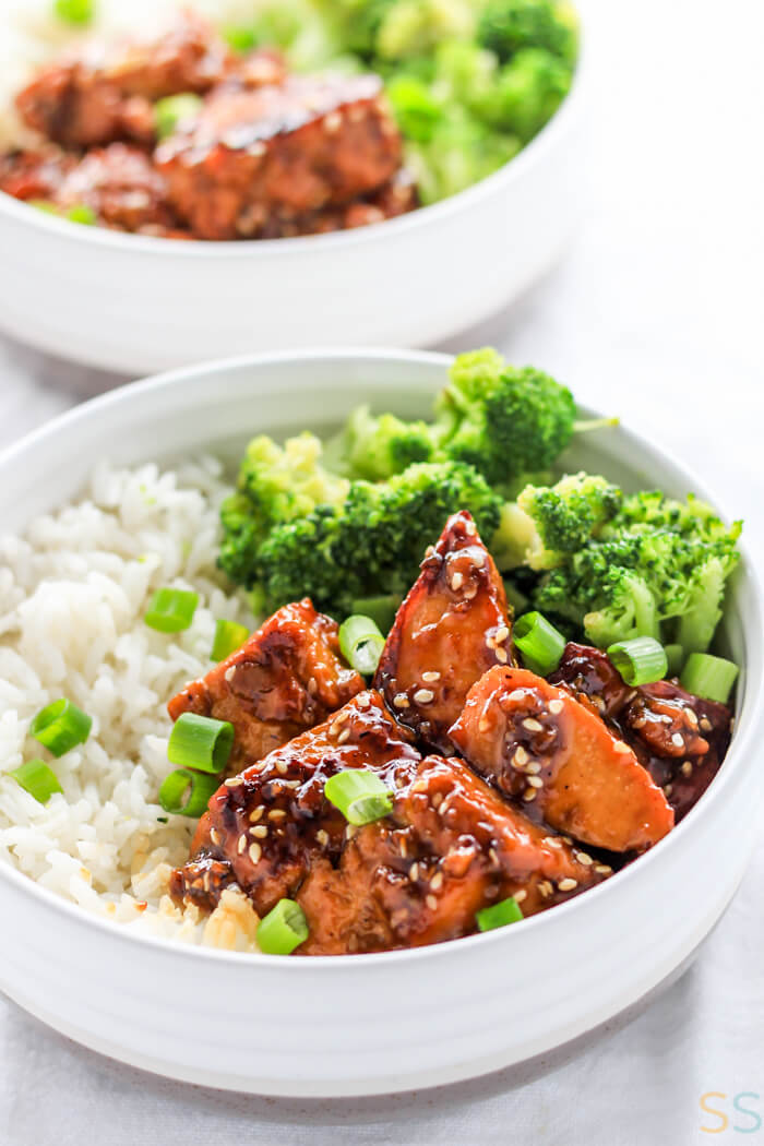 bowl of teriyaki tofu with rice, broccoli, and topped with sesame seeds and chopped green onions.