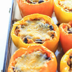 Bright yellow peppers stuffed with a mexican stuffing and topped with melted cheese on a sheet pan