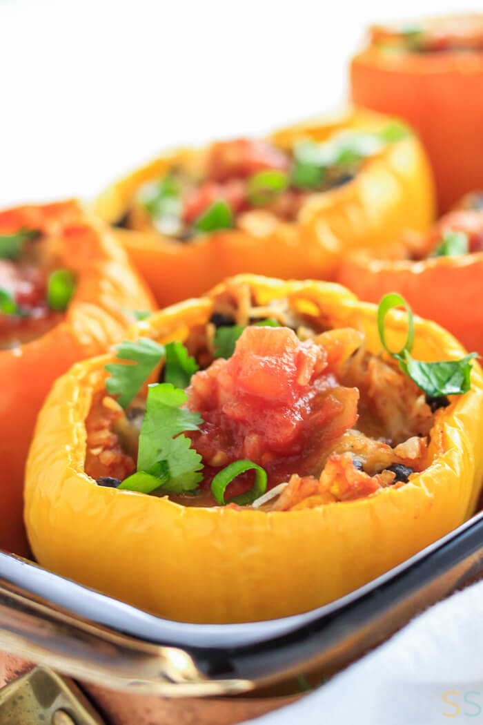 black bean Mexican stuffed pepper topped with cilantro, green onion and salsa.