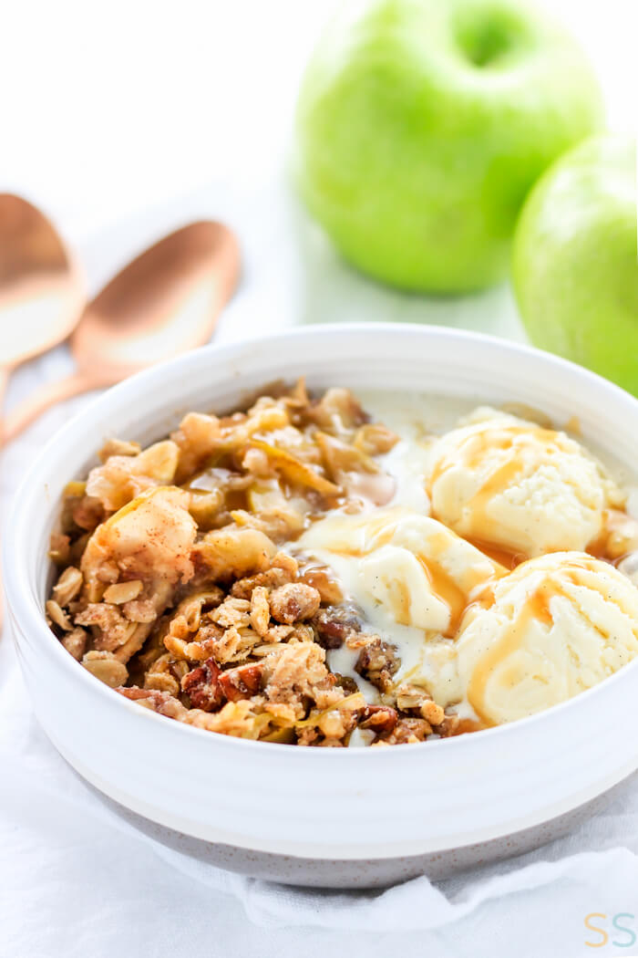 bowl of the no peel apple crisp with ice cream and caramel sauce with green apples in the background.