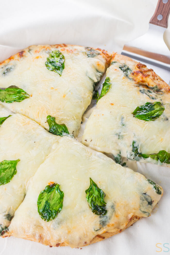 Slices of spinach Alfredo Sauce pizza on a cutting board.