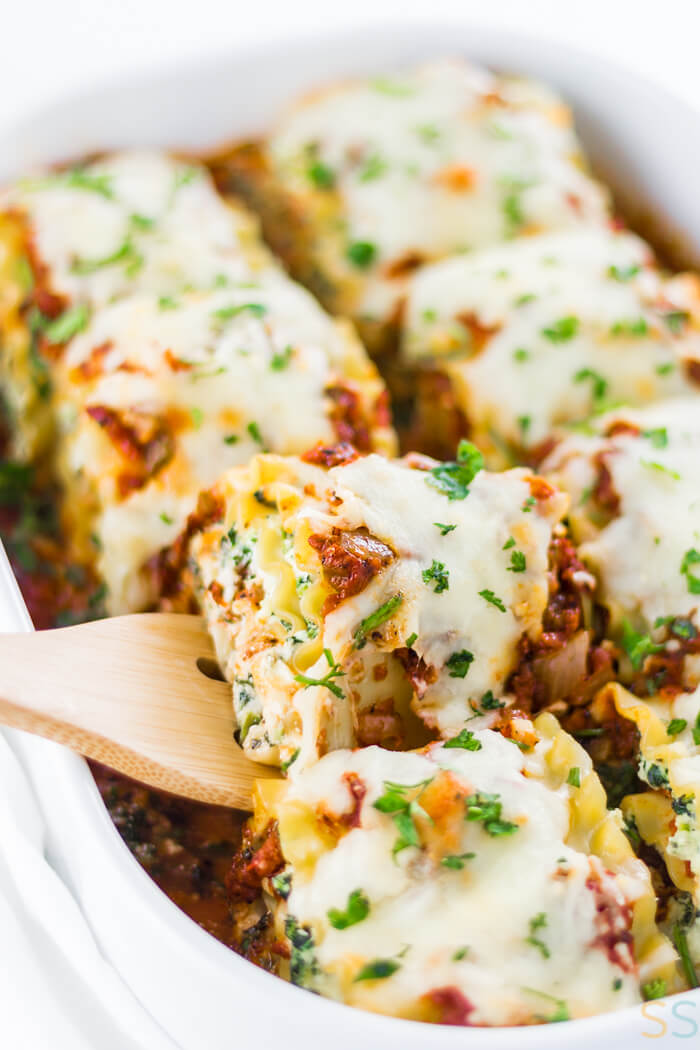 baking dish with spinach lasagna rolls topped with parsley.