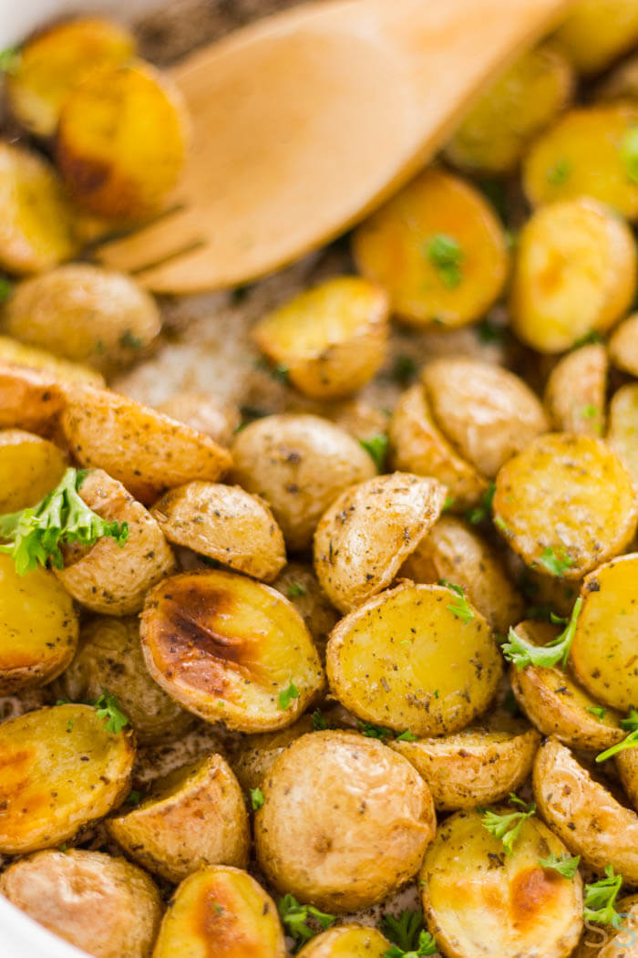 Wooden Spoon with a sheet pan of roasted tiny potatoes. Perfectly roasted.