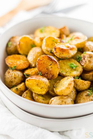 white bowl of honey gold potatoes roasted in the oven and topped with a bright green garnish