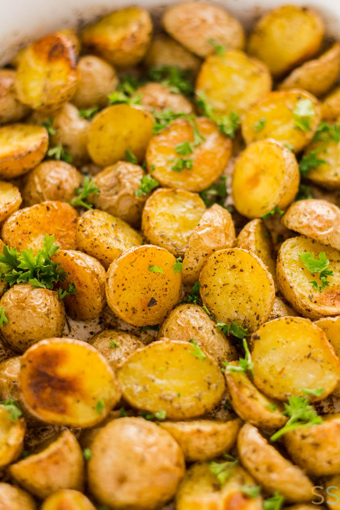 oven roasted honey gold potatoes cut in half and topped with parsley in a bowl.