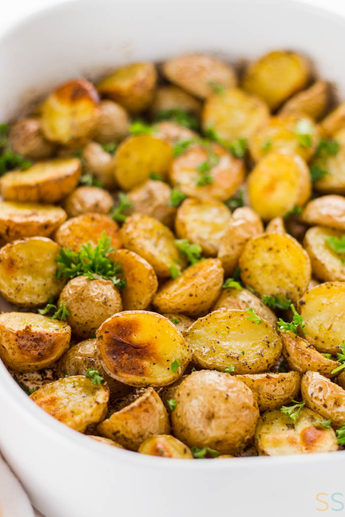 white serving dish with potatoes cut in half, seasoned and roasted to a golden brown.
