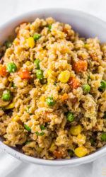 Bowl of cauliflower rice with frozen peas carrots and corn mixed in