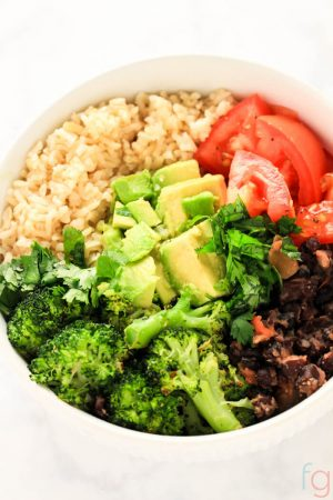 Easy Vegan Buddha Bowl filled with rice, broccoli, tomatoes and avocado in a white bowl