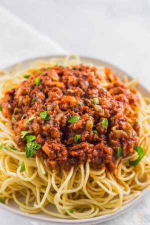 bowl of spaghetti topped with this vegan sauce on a white plate