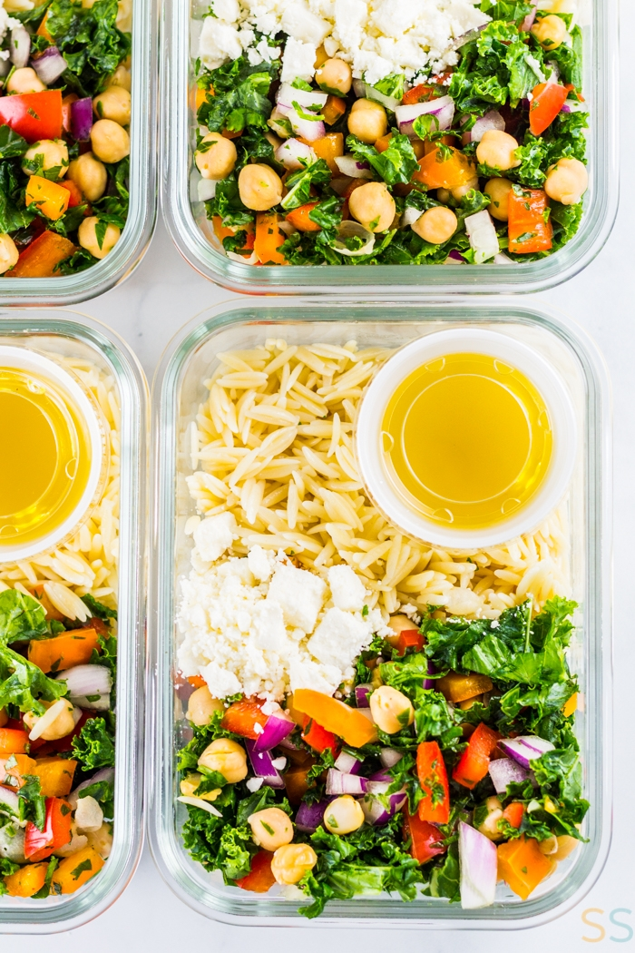 Orzo, chickpea salad, cheese and salad dressing in glass meal prep containers.