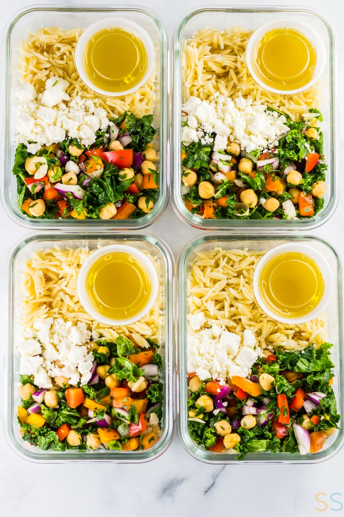 four glass meal prep containers with orzo, salad dressing, cheese and the salad mix.