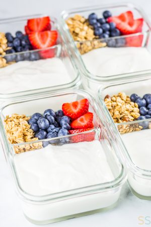 Four glass breakfast meal prep containers with yogurt on one side and granola, strawberries and blueberries on the other