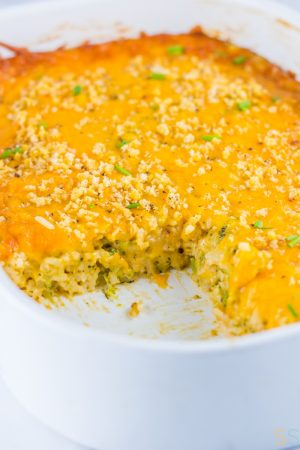 White casserole dish with one piece of the cheesy broccoli casserole removed