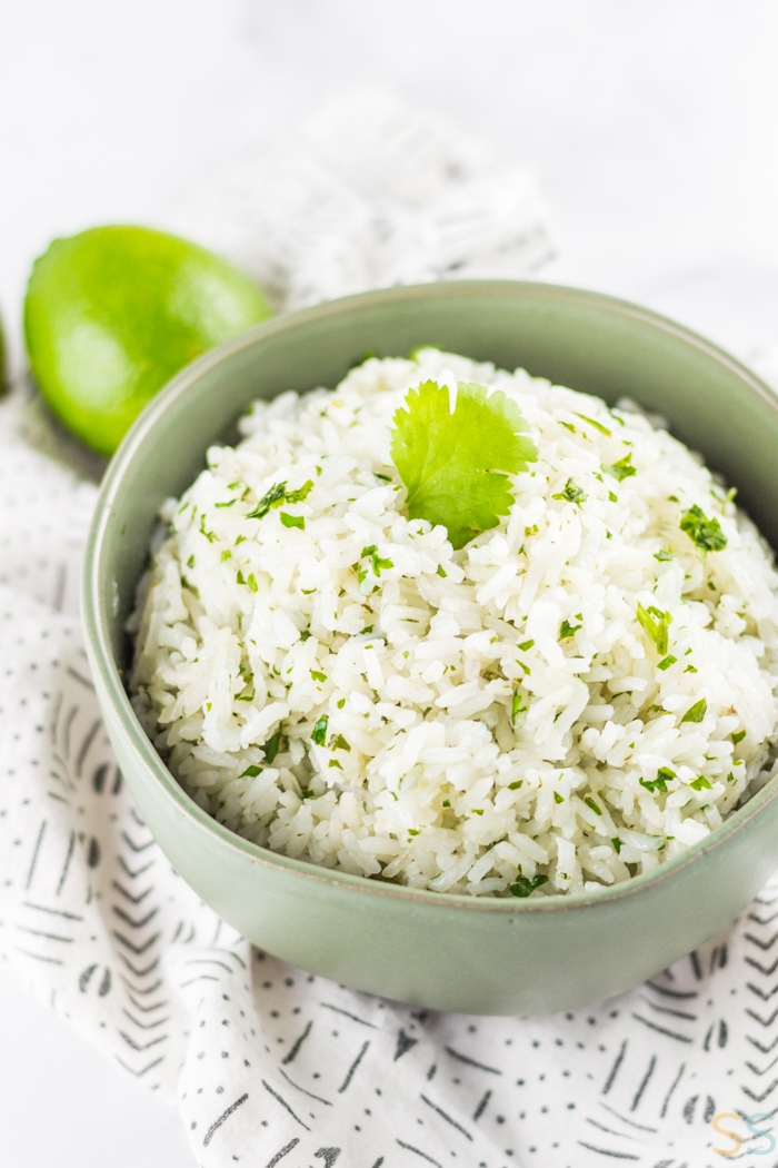 Bowl of cilantro lime rice in a grey bowl and limes in the background