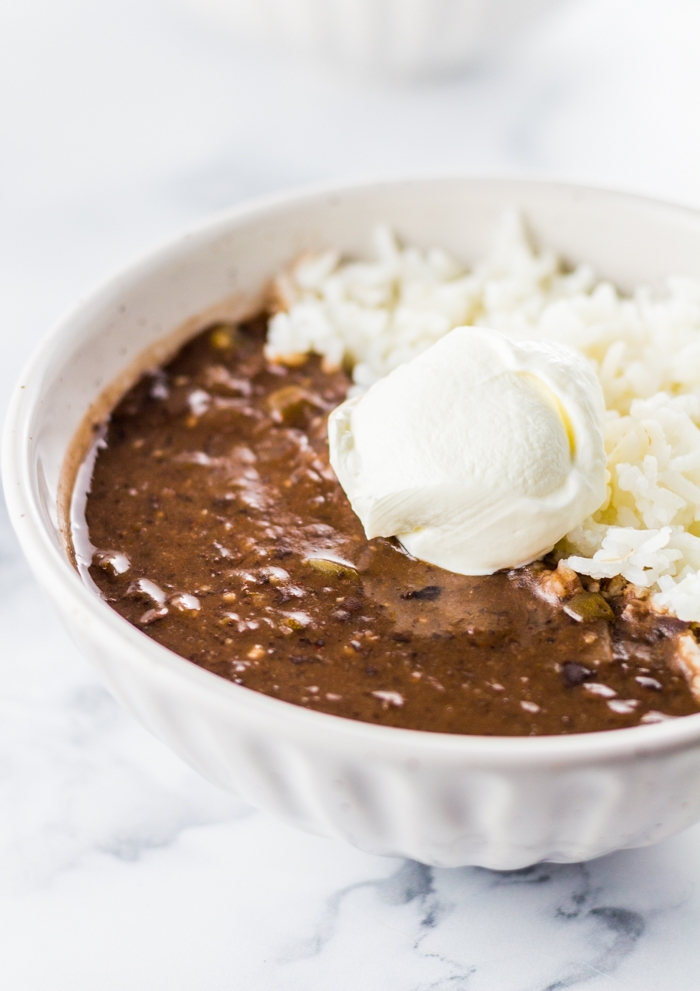 Bowl of Slow Cooker Black Bean Soup in a white bowl with rice and sour cream.