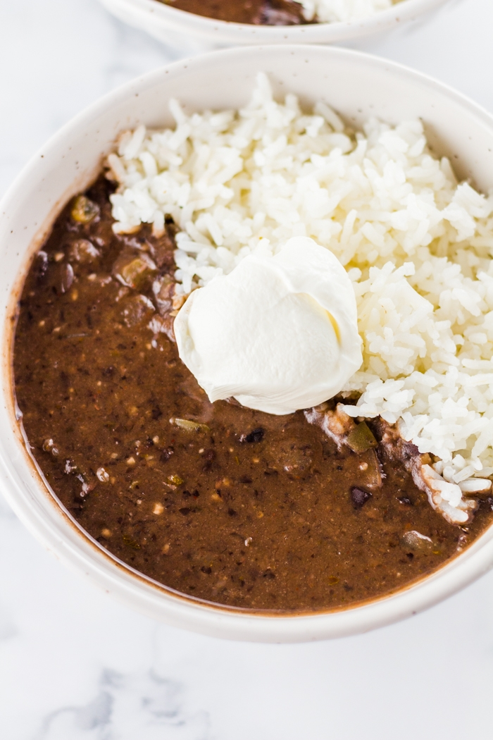 black bean soup made in the slow cooker in a white bowl with rice and topped with sour cream.